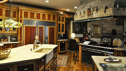 The kitchen flows into one large space detailed with curly cherry and handcrafted cabinets with butternut wainscot molding. Durango limestone counterops with a deep stone sink and three stainless steel sinks are also featured.