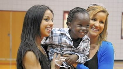 Jamie McMutrie, left, and her sister Ali McMutrie hold their new brother, Fredo, 4, of Haiti, after ceremonies announcing a new scholarship in their honor were held at Avonworth High School.