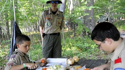 Martin Raitt, left, 10, and Joey Calabro, 14, right, chop carrots for dinner as Eric Hochendoner,  center, 15, looks on.