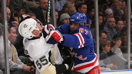 Penguins defenseman Sergei Gonchar is checked along the boards by Rangers forward Donald Brashear.