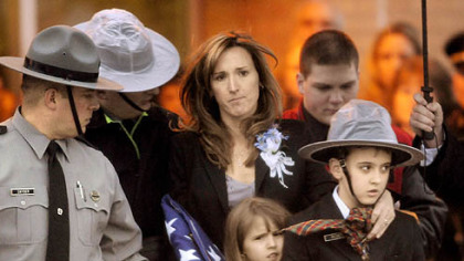 Carrie Cornell, widow of Pennsylvania State Trooper Paul. G. Richey, and her children Conner, 9, and Catherine, 6, leave yesterday's funeral at Franklin Area High School.