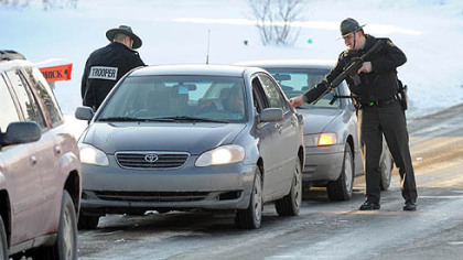 Two Pennsylvania State Police troopers search cars coming from Bredinsburg Road as part of a manhunt for the man who killed a fellow state trooper.