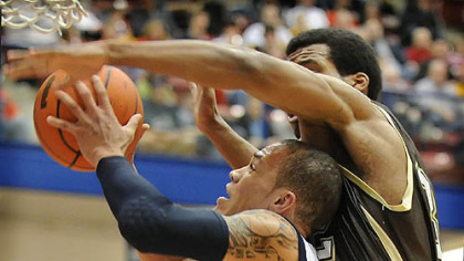 Duquesne's Bill Clark goes up against St. Bonaventure's Michael Davenport.