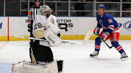 Penguins goaltender Marc-Andre Fleury makes a glove save against as Rangers forward Sean Avery moves in.