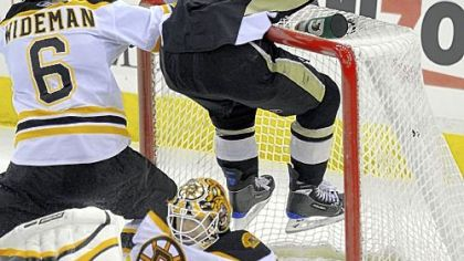 Penguins' Chris Kunitz flies into the upper crossbar over Bruins goaltender Tim Thomas.