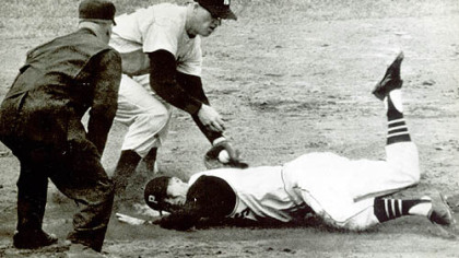 Don Hoak slides into second in the fourth inning of the second World Series game against the New York Yankees. Trying to put the ball on him is Tony Kubek, with Umpire Nestor Chylak calling the play.