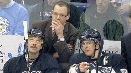 Penguins coach Dan Bylsma, center, listens as Sidney Crosby, right, talks on the bench with teammate Bill Guerin during the first period of a game against Detroit in January.