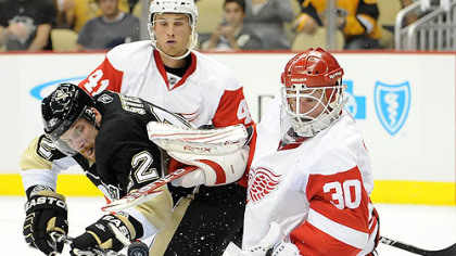 Penguins forward Brett Sterling is stopped by Red Wings goaltender Chris Osgood at Red Wings forward Ilari Filppula defends in the first period of Tuesday's game at Consol Energy Center.