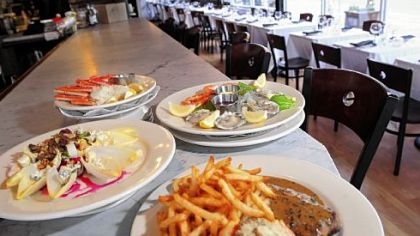 Among selections at Brasserie 33 are beet and endive salad, left, plateau de fruits de mer, and steak frites, right.