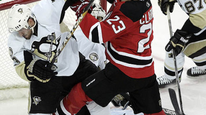 Devils forward David Clarkson Penguins defenseman Alex Goligoski out of the crease as Penguins goaltender Brent Johnson looks for the puck in the second period.