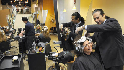 Emilio Cornacchione, right, proprietor of Izzazu salon, works on client Denis Robinson's hair in the salon's new digs next to the Capital Grill on Fifth Ave.