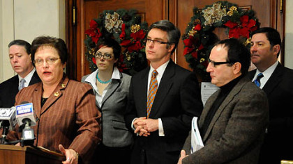 Flanked by Pittsburgh Controller Michael Lamb, left, and other council members, Pittsburgh City Council President Darlene Harris announces a plan that will avoid a state takeover of Pittsburgh's pension plan.