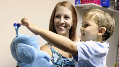 Megan Naughton of Ross holds her son, Duncan, 3, as he interacts with Popchilla, a robot at the Autism Center of Pittsburgh in McCandless. The robot is used to help children with autism with limited or no verbal skills.