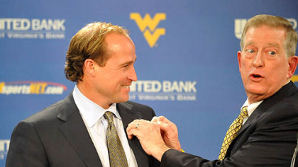 Dana Holgorsen, left, West Virginia's new offensive coordinator and quarterbacks coach receives a West Virginia pin from head coach Bill Stewart yesterday in Morgantown, W.Va.