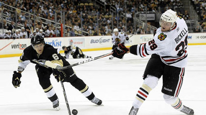 Blackhawks left wing Bryan Bickell  takes a shot as Penguins defenseman Ben Lovejoy pressures during the first period.