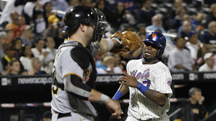 The Mets' Jose Reyes races home to score on Angel Pagan's second-inning double, as Pirates catcher Chris Snyder waits for the throw.