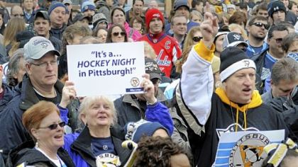 Patti Koerbel from Gibsonia (with sign) and Dan Zadach from Jefferson Hills (full Pens garb) were among the fans who thronged Market Square for the Penguins rally Thursday ahead of the Winter Classic against the Washington Capitals on Saturday.
