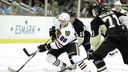 Blackhawks forward Patrick Kane handles the puck against Penguins forwards Evgeni Malkin Mike Comrie.