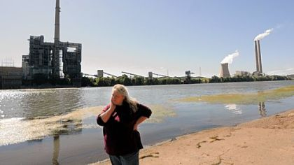 Elisa Young stands along the banks of the Ohio River in Meigs County, Ohio, with the Philip Sporn and Mountaineer power plants on the West Virginia side of the river. There are two other power plants on the Ohio side of the river.