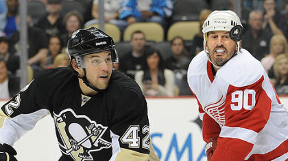 Penguins forward Eric Tangradi battles for loose puck with Red Wings forward Mike Modano.