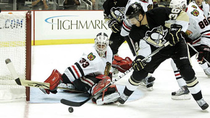 Blackhawks goaltender  Hannu Toivonen makes a save against Penguins forward Nick Johnson.