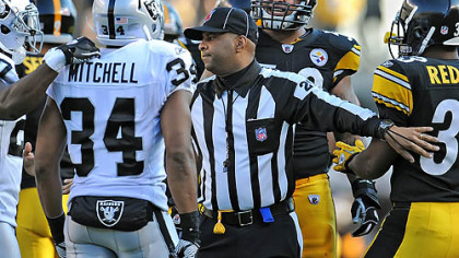 Line judge Adrian Hill has to separate Maurkice Pouncey and Mike Mitchell of the Raiders Sunday at Heinz Field.