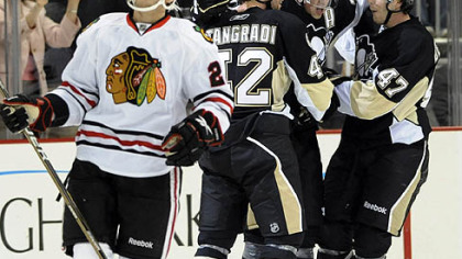 Blackhawks left winger Jeremy Morin  watches the replay as Penguins forward Eric Tangradi, Simon Despres, right, and Evgeni Malkin celebrate after Malkin scored during the first period.