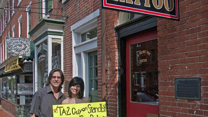 Rose Ann Belluso and her husband, Jim, stand in front of X-Treme Ink Tattoo in West Chester, Pa., with the sign Rose Ann used to get her back signed by Paul McCartney during a concert Sunday night in Philadelphia.