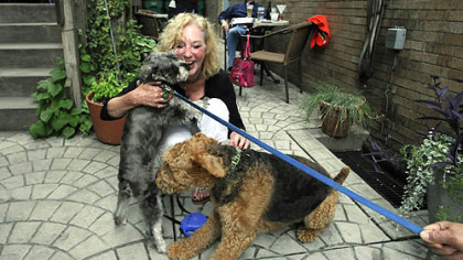 Aleppo's Carolyn Smith gets a kiss from Samson Amadeus, left, as her own dog, Sophie, gets social, too, at the Bowl and Biscuit Night at Cassis restaurant on the North Side.