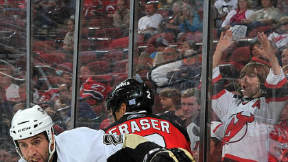 Devils defenseman Mark Fraser is checked by Penguins forward Maxime Talbot #25 during the third period.