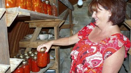 Shelba Fullmer, of Arthurdale, W.Va., with some of the hot peppers and tomato sauce  she canned this summer.