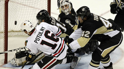 Blackhawks forward Ryan Potulny can''t get a shot by Penguins goaltender Brent Johnson in the first period as as Penguisn forward Mike Comrie and Eric Tangradi defend.