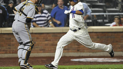 The Mets' Ruben Tejada scores the winning run in front of Pirates catcher Ryan Doumit on a single by Nick Evans in the 10th inning.
