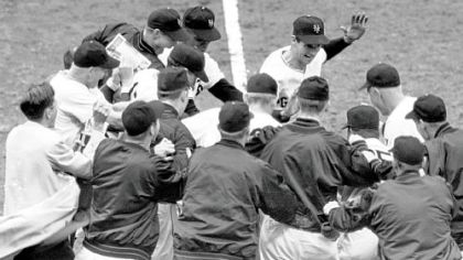 This Oct. 3, 1951, file photo shows the New York Giants baseball team greeting teammate Bobby Thomson, center rear with hand raised, after Thomson's ninth-inning homerun against the Brooklyn Dodgers, to give his team a 5-4 victory and a trip to the World Series, at the Polo Grounds in New York.