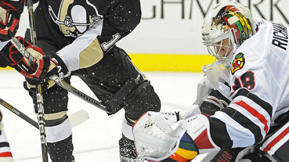 Penguins forward Mike Comrie battles for a loose puck in front of Blackhawks goaltender Alec Richards during Tuesday's game at Consol Energy Center.