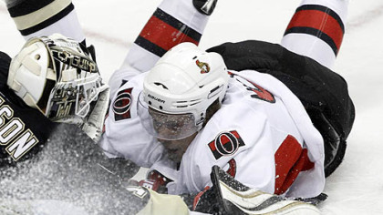 Senators forward Milan Michalek slides into Penguins goaltender Brent Johnson in the first period.