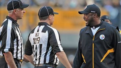 Steelers head coach Mike Tomlin has words with Greg Wilson, the back judge, and Gary Cavaletto, the field judge, during Sunday's game against Oakland.