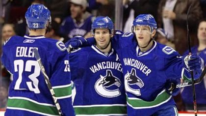 "Vancouver Canuck Ryan Kesler, center, celebrates his goal with teammates Alexander Edler, left, and Christian Ehrhoff during a March game. Kesler is the cover athlete of the video game ""NHL 2K11,"" due out next week."
