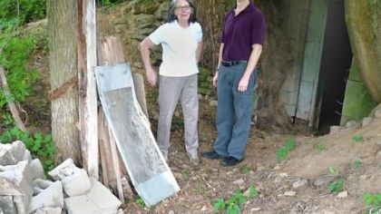 Kathleen Sullivan and Greg Galford stand in front of the root cellar entrance at Eden Hall Farm.