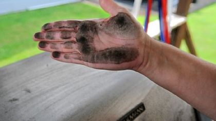 Stacy Beisler's hand is covered with black soot she wiped from her backyard grill, which she had cleaned two days earlier.