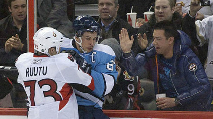 Senators forward Jarkko Ruutu checks Penguins captain Sidney Crosby into the boards during the second period of Sunday's game at Scotiabank Place in Ottawa.