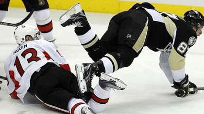 Penguins captain Sidney Crosby collides with Senators forward Peter Regin in the first period.
