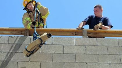 Seth Haskins, 17, a student in the Forbes Road Career and Technology Center emergency response program, lifts a fire hose to the fire tower as Chris Pearce, 18, watches during a practice drill at the school in Monroeville.