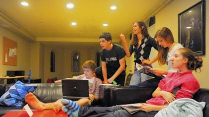 Cameron Clark, left, works on his computer as, from left to right, Seth Klein-Tooley, 13, Alyssa Drake, 16, Erin Young, 17, and Aidan Schubert, 16, watch television in a common room at the Pittsburgh Ballet Theatre's Byham house for out-of-town students.