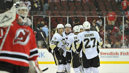 Devils goaltender Martin Brodeur skates back to goal as Penguins defenseman, Paul Martin is congratulated after scoring an empty net goal in the third period by teammates Kris Letang, Chris Kunitz, Sidney Crosby and Craig Adams Monday at the Prudential Center in Newark, N.J.