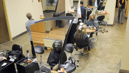 Emilio Cornacchione, bottom right, proprietor of Izzazu salon, works on client Denis Robinson's hair in the salon's new digs next to the Capital Grill on Fifth Ave.
