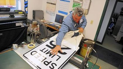 Sign maker Pete Shandrick pulls a cover off of a speed limit sign he created inside his office in the Moon Public Works garage.