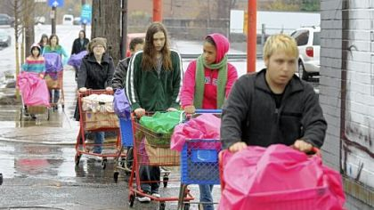Braving Sunday morning's pouring rain, young people from the Allegheny Unitarian Universalist Church push carts containing 100 bags of groceries to the Northside Common Ministries Food Pantry on Brighton Road.
