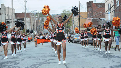 Ashae Berry, 16, leads the Clairton cheerleaders along Miller Avenue to the Clairton stadium before a home game Sept. 24 against Chartiers-Houston.