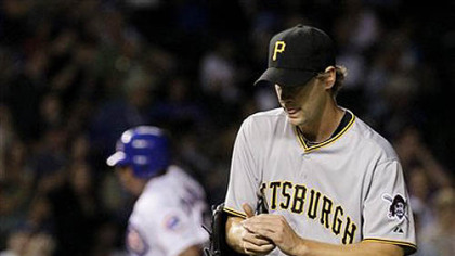 Pirates relief pitcher Brian Burres returns to the mound after giving up a two-run homerun to Chicago Cubs' Carlos Zambrano, background, that also scored  Koyie Hill, during the fifth inning of last night's game at Wrigley Field in Chicago.